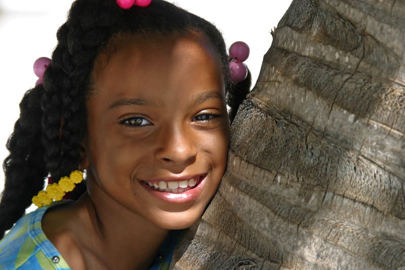 Girl simling while leaning against coconut tree in San Pedro, Ambergris Caye, Belize.