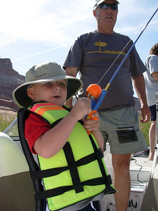 Chuck Fulton of Prescott AZ coaches his grandson on reeling in a striper at Lake Powell. 5-25-07, Utah Division of Wildlife Resources.