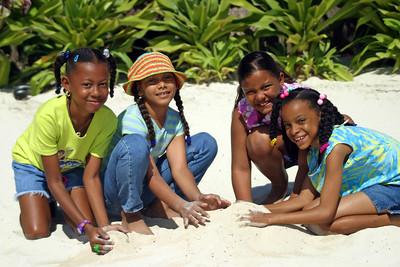 Girl friends building sand castles in San Pedro, Ambergris Caye, Belize.