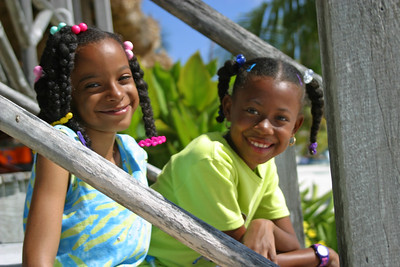 Two girls on steps smiling in San Pedro, Ambergris Caye, Belize.