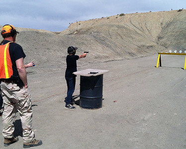 A young shooter fires off ten rounds from a pistol in order to knock down a row of metal plates during the Green River 3-gun Shoot Competition. Photo taken 04-12-14 by Brent Stettler, Utah Division of Wildlife Resources.