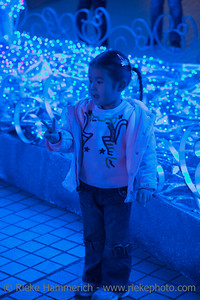 Little Chinese Girl showing Victory Sign - Illuminated from Blue Lights in Hong Kong