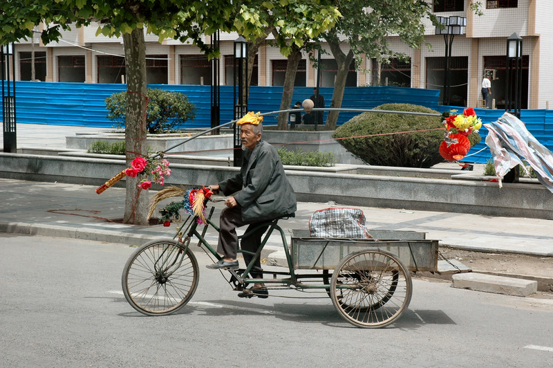 In Huxian in Central China this old man seems to amuse villagers but is regarded disdainfully as the village eccentric.<br /> <br /> ©Gerald Diamond<br /> All rights reserved