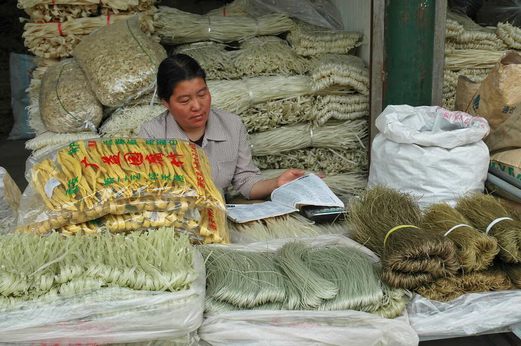 Woman selling noodles of all kinds at a stall in a Xian market - China<br /> <br /> ©Gerald Diamond<br /> All rights reserved