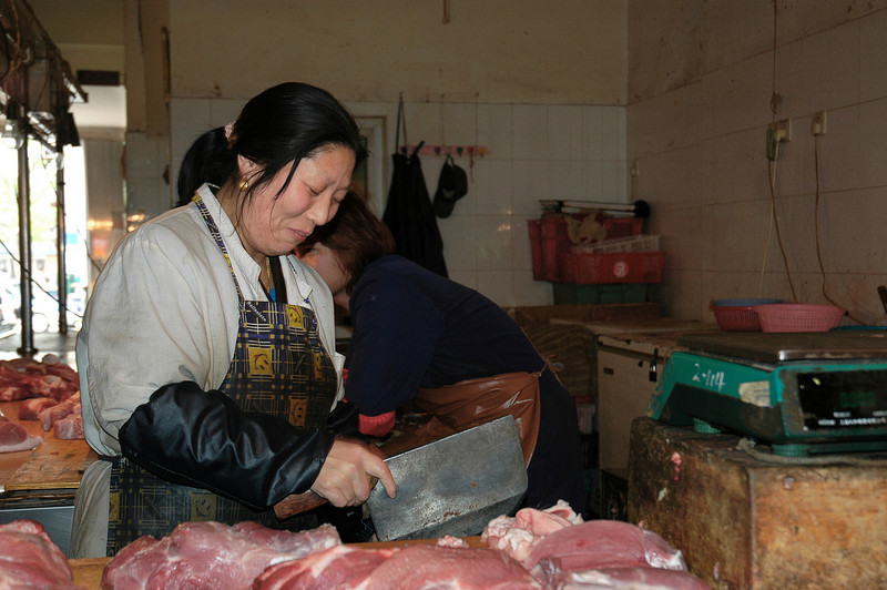 Butcher in Shanghai fresh food market.<br /> <br /> ©Gerald Diamond<br /> All Rights Reserved