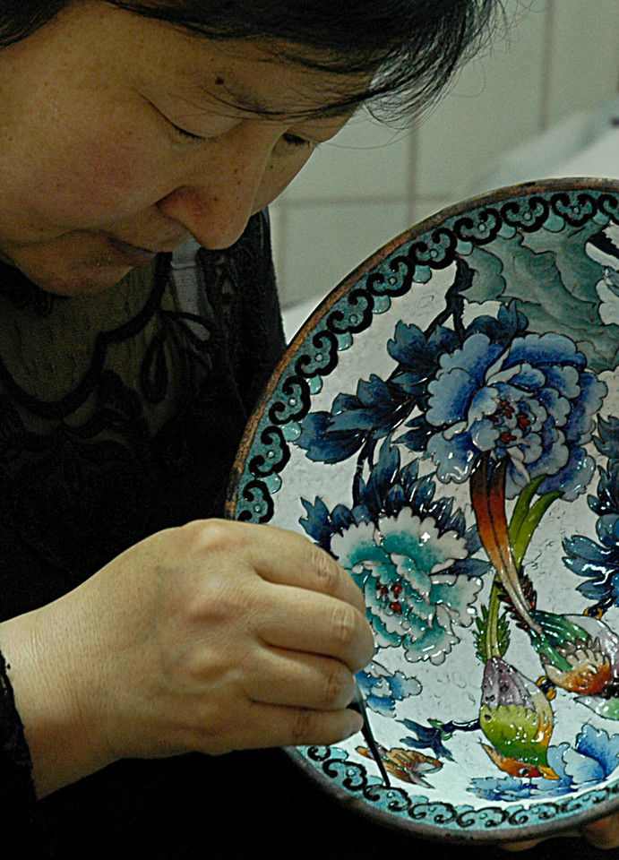 A craft worker engaged in the fine work of cloisonné, painting damp enamel powder in the grooves between copper filaments - Beijing, China<br /> <br /> ©Gerald Diamond<br /> All rights reserved