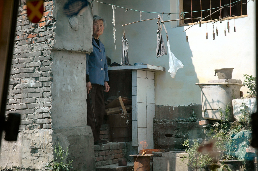 The Chinese are often very curious about foreigners though rarely as shy as this woman peeking out from her home, watching a tourist boat cruise slowly by on one of Suzhou's many waterways.  Suzhou, China<br /> <br /> ©Gerald Diamond<br /> All rights reserved