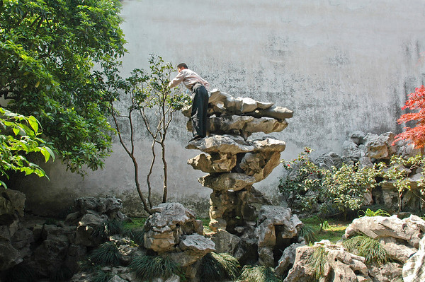 """An attendant pruning a tree in the """"Garden Of The Master Of The Nets"""" in Zhoujiaojiao, south of Shanghai, China.  ©Gerald Diamond All rights reserved"""