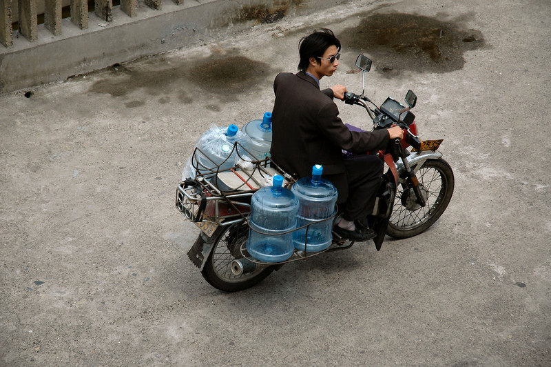 Motorcycles are yet another form of transportation pressed into service for moving goods around cities in China.  Here a man is delivering water as he crosses the dam at Yi Chang on the Yangtze River.<br /> <br /> ©Gerald Diamond<br /> All rights reserved