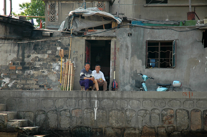 These men are relaxing, watching the world pass by on one of Suzhou's many canals.  Notice the rolled up pant leg.  Men in China often roll up their pant legs or roll up their shirts from the waist to their underarms.  This is how one manages when one cannot afford different clothing for different weather conditions. Suzhou, China (south of Shanghai).<br /> <br /> ©Gerald Diamond<br /> All rights reserved