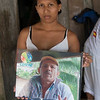 Mario Castaño's daughter Nelcy was present the day her father was murdered on Sunday 26 November 2017. After that day, she and her daughters and her mother and sister moved, and now they are waiting for guarantees that they can return to the farm in safety. During the visit, a tribute was held to the leader and his struggle to recover his property, Arbol del Pan, in the village of La Madre, part of the collective territory of La Larga y Tumaradó.<br /> In this photo Nelcy is holding a picture of her father.