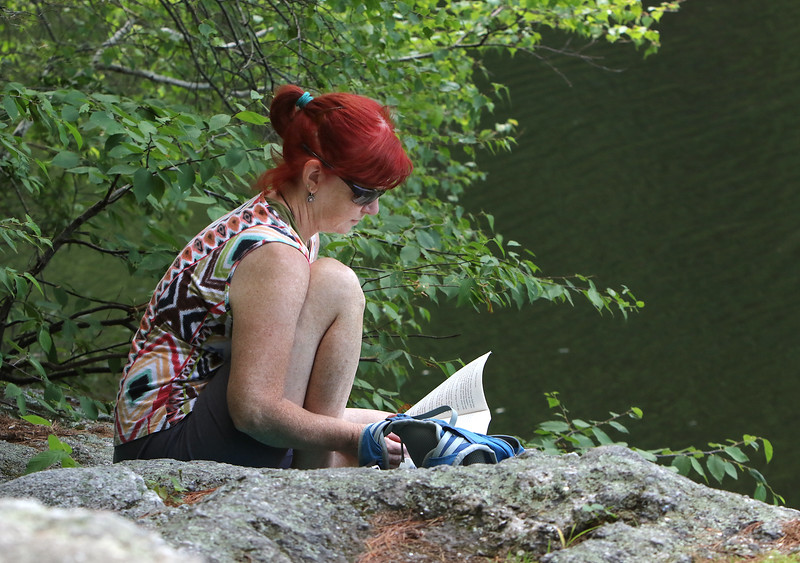 """April Estabrooks of Leominster reads """"The Sunday Potluck Club"""" sitting by Mirror Lake in Coggshall Park in Fitchburg.  (SUN/Julia Malakie)"""