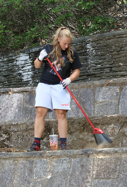 Features around Mirror Lake in Coggshall Park in Fitchburg.  Jordyn Trombly, 19, of Worcester sweeps the amphitheatre at the gazebo Thursday ahead of her uncle's wedding on Saturday. She was there with her mother and grandfather. They heard the park was maintained by volunteers so they decided to volunteer. (SUN/Julia Malakie)