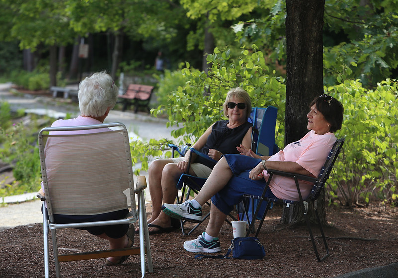 Features around Mirror Lake in Coggshall Park in Fitchburg. Anne Shattuck of Lunenburg, left, Marie Turmaine of Leominster, right, and Rita Jackey of Westminster, rear, are members of the Hot Flashes chapter of the Red Hat Society, who come to the park for a social distanced visit every Thursday. It's usually a larger group, but this week the others were busy. (SUN/Julia Malakie)