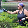Features around Mirror Lake in Coggshall Park in Fitchburg.  Kate Trombly of Worcester trims shrubs at the gazebo Thursday ahead of her brother's wedding on Saturday. She was there with her father and daughter. They heard the park was maintained by volunteers so they decided to volunteer. (SUN/Julia Malakie)