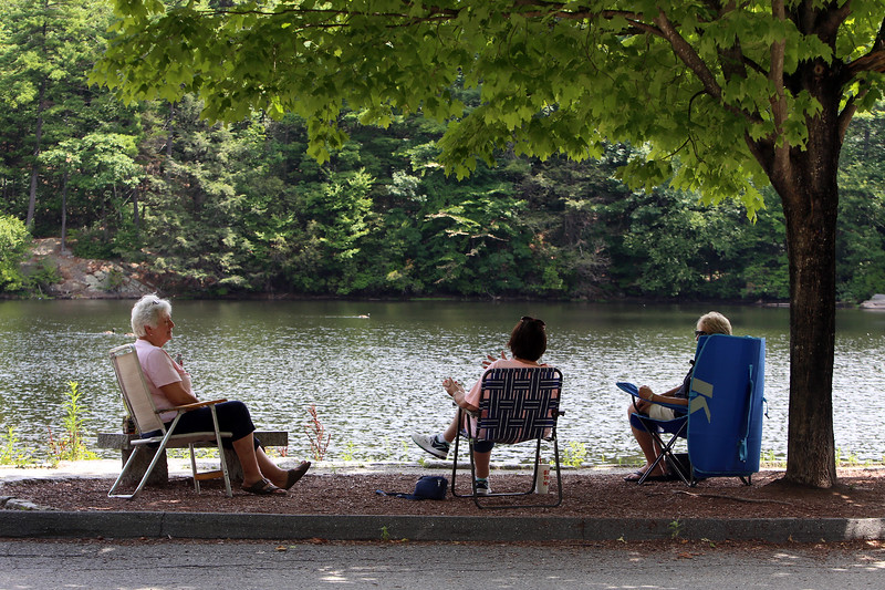 Features around Mirror Lake in Coggshall Park in Fitchburg. From left, Anne Shattuck of Lunenburg, Marie Turmaine of Leominster, and Rita Jackey of Westminster, are members of the Hot Flashes chapter of the Red Hat Society, who come to the park for a social distanced visit every Thursday. It's usually a larger group, but this week the others were busy. (SUN/Julia Malakie)