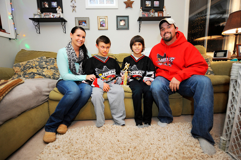 Connor McKenna, 14, of Leominster (2nd from left), who is blind and uses a wheelchair, sits with his mother Kirstin Mitton, his step-brother Tucker Mitton, and his step-father Rob Mitton at their home, Friday night. Tucker's Twin City youth hockey team dedicated last weekend's tournament to Connor, rallying around him in the locker room before games, and gave the tournament trophy to him.<br /> SENTINEL & ENTERPRISE / BRETT CRAWFORD