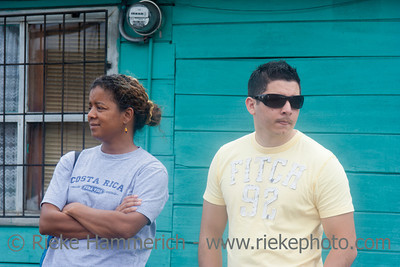 SAN JOSE, COSTA RICA - AUGUST 31: Couple with communication problems standing side by side in front of  wooden building in San Jose, Costa Rica on August 31, 2008. They are waiting for the bus.