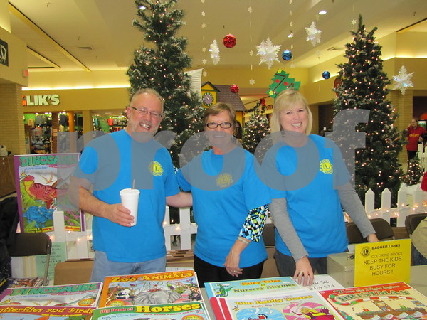 Larry Paul, Lori Gascho, and Kristi Bruen of the Badger Lions Club were selling giant coloring books.