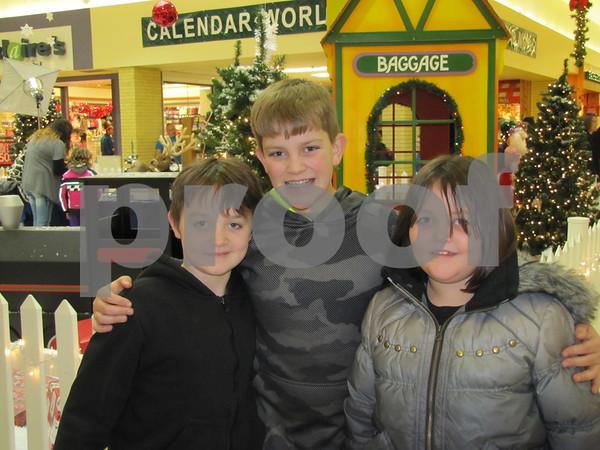 Harley, Seth, and Alison Neuman posed outside Santa's visiting booth.