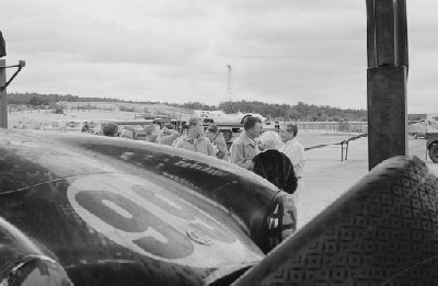 Bridgehampton Double 500, 1963. In the foreground, race number 99, Shelby Cobra driven by Bob Holbert. Behind, Carroll Shelby (tan jacket with badge) speaks with Briggs Cunningham (white racing suit) In the background is race number 62, Cooper Monaco T57 driven by Paul Richards. (Photo credit: Karl Ludvigsen Photograph Collection, Revs Institute)