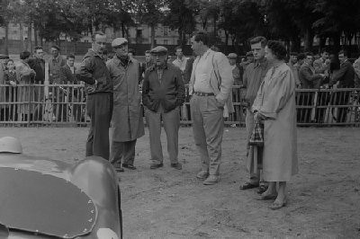24 Hours of Le Mans, 1954. Pre-race technical inspection area, left to right: John Gordon Bennett, co-driver (jacket, hand on right hip); Briggs Cunningham , co-driver (hat, overcoat, hands behind back); Alfred Momo, team manager (hat, glasses, hands in pockets); Bill Spear, co-driver ( sport coat, hands in pockets); Sherwood Johnston, co-driver (jacket, right hand in pocket); Mrs. John Gordon Bennett (hat, overcoat, holding purse). (Photo credit: George Phillips Photograph Collection, Revs Institute)