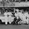 "24 Hours of Le Mans, 1950. Pit scene, (Car Number 3), the Cadillac Series 61 ""PETIT PATAUD"", (Sam Collier and Miles Collier, co-drivers); left to right: Jean Oliveau, team member (glasses, shirt/tie, coverall, standing); Sam Collier, driver (hat, sunglasses, coverall, standing); Miles Collier, driver (watch on left wrist, coverall, standing); Bill Spear, team member (hat, glasses, standing); Phil Walters, driver (dark shirt/trousers, kneeling); Briggs Cunningham, driver (dark shirt, light trousers, kneeling); Alec Ulmann, team member (watch on left wrist, coverall, kneeling). (Photo credit: Smith Hempstone Photograph Collection, Revs Institute)"