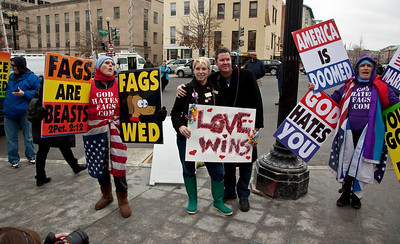 "Newlyweds Morgan Murphy and Todd Williamson from DC. hold Love Wins sign amid anti gay protestors. They are a straight couple that had ""boycotted marriage for 6 years until everyone can marry and today's the first day""."