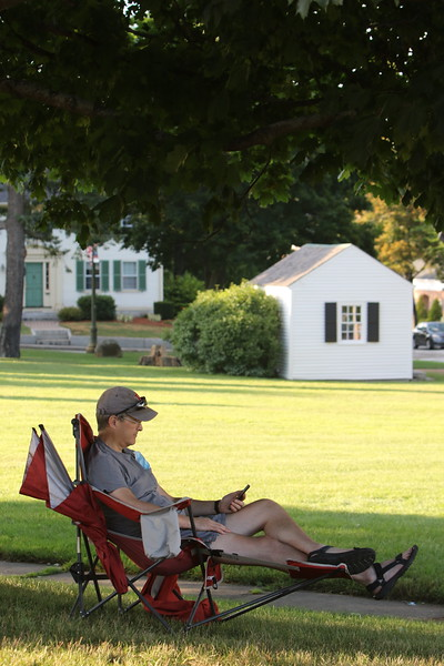 Steve Bower of Westford reads in the shade of a tree at Chelmsford Town Common. His 12-year-old son, nephew, and a friend were in Chelmsford Center doing Pokemon Go. (SUN/Julia Malakie)