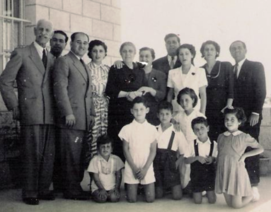 Abe Assily, front and center, wearing all white, is pictured with his extended family at the 4-story home his father and uncles built in West Jerusalem, Palestine. They were forced to evacuate the house in 1949 after the state of Israel was established.