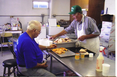 Avery Wilcox Sr. (standing right) and fellow Old Glory Grange member Virgil Tompkins (seated left) worked in the kitchen of the Lorain County Fair cafeteria in 2004. (Photo courtesy of the family.)