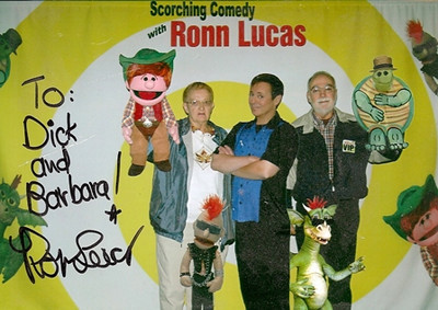 Barb and Dick Baldwin, shown on either side of entertainer Ronn Lucas, posed with the puppeteer and his cast of puppet characters for this autographed picture.