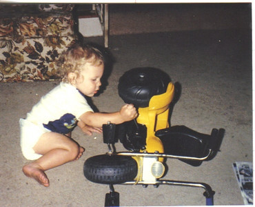 Craig, 2, pretends to fix his plastic tricycle.