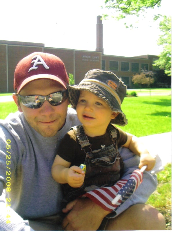 Craig Behrend and his 1-year-old son, Mark, sit in front of Avon Lake High School for the Memorial Day parade in 2008.