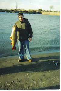 Craig Behrend shows off a 20-pound fish that he caught near CEI's Avon Lake Power Plant in April 2002.