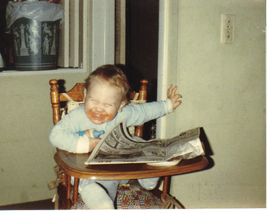 Craig Behrend, age 1, appears to have found something amusing in the newspaper in December 1984.