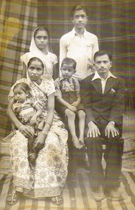 D.C. Patel, seated and barefoot, is surrounded by his family in this photo taken during a visit to India in 1950. Seated are his parents with his mother holding his little sister. Two cousins stand behind them.