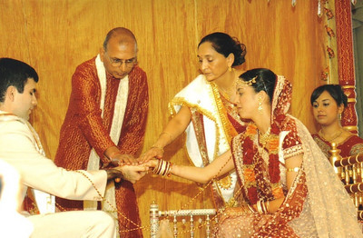 D.C. Patel and his wife, Minal, standing, take part in a Hindu wedding ceremony for their daughter, Rachna, and her groom, David Fruchbom. Their second daughter Rakhee is on the far right.