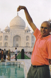 DC Patel playfully appears to hold up the Taj Mahal with his fingers.
