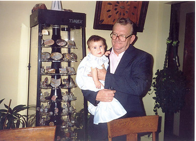 Frannie Grim holds his granddaughter Arika next to a display case filled with his lapidary art.