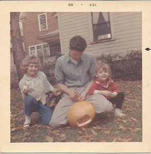 Harris Opfer shows his foster daughters, Donna and Debbie, how to carve a pumpkin in 1966. (Photo courtesy of the family.)