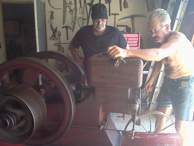 Harris Opfer, right, and his stepson, Brett Britton, work on an old hit-and-miss engine, one of Harris' most recent hobbies, in 2011. (Photo courtesy of the family.)