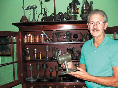 At one time, Harris Opfer collected antique oil lamps. Here he shows a lard oil lamp that was patented on Feb. 4, 1851, in Circleville. (File Photo by Melissa Linebrink, The Chronicle-Telegram.)
