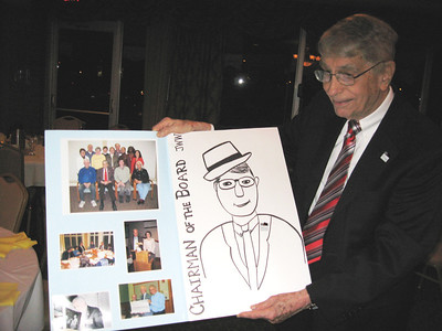 """Jim White opens his """"retirement"""" card, signed by dozens of well-wishers, at the Oberlin Heritage Center's Annual Meeting in April 2010 at the end of his term as Board President. (Photo courtesy of Oberlin Heritage Center.)"""