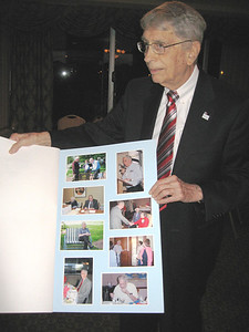 """Jim White shows more of his """"retirement"""" card, signed by dozens of well-wishers, at the Oberlin Heritage Center's Annual Meeting in April 2010 at the end of his term as Board President. (Photo courtesy of Oberlin Heritage Center.)"""