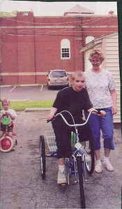 Micah Black riding his 3-wheeler, while his brother, Christopher, rides his tricycle and their mother, Diane, watches.