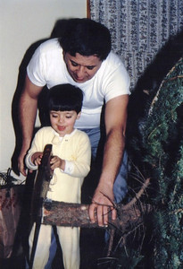 Pat Ziroli teaches his son, Anthony, how to use a saw to make the bottom of the Christmas tree level. (Photo courtesy of the family.)