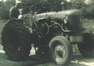 Paul Dziak lets his son Ron pretend to drive a tractor that he used while working for the Sheffield Township road department.