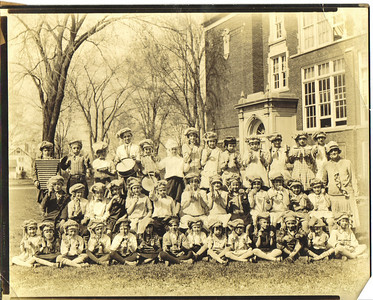 Ray Church, far left, second row, is pictured in the 1920s with dozens of other kids, wearing similar hats and holding percussion instruments, and a woman, who apparently was their teacher. His children would like to know more about this group.