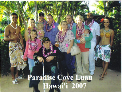 Ray Church, seated, is surrounded by family and two luau workers during a trip to Hawaii in 2007.